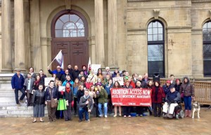 New Brunswick marked the World March of Women 2015 day of action by rallying for equality and solidarity at the NB Legislature on April 24, 2015. The focus of World March of Women 2015 is precarious work. April 24, 2015 marks the 2nd anniversary of the factory collapse in Bangladesh that killed 1,135 workers. Present at the rally were CUPE NB, the Common Front for Immigrant Women & Visible Minorities, the Common Front for Social Justice, Early Childhood Care & Education New Brunswick, Fredericton Gender Minorities Group, Fredericton Youth Feminists, the Maritimes-Guatemala Breaking the Silence Network, the NB Coalition for Pay Equity, Regroupement féministe du Nouveau-Brunswick and Reproductive Justice NB. Organizers are planning a march in October. Photo by Sophie M. Lavoie.